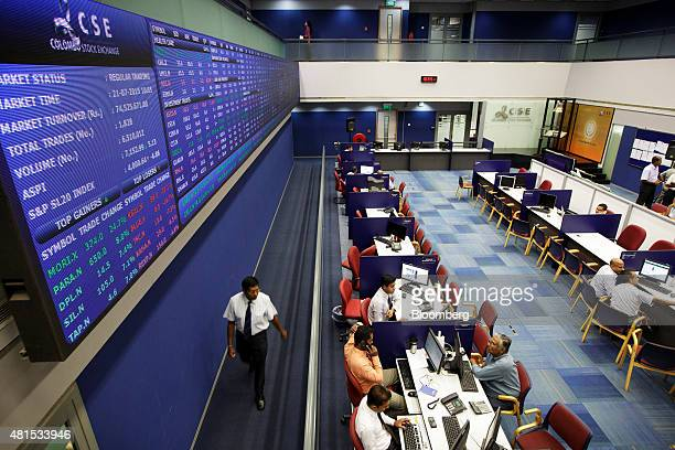 Traders sit below an electric stock board while working on the floor of the Colombo Stock Exchange in the central business district of Colombo Sri...