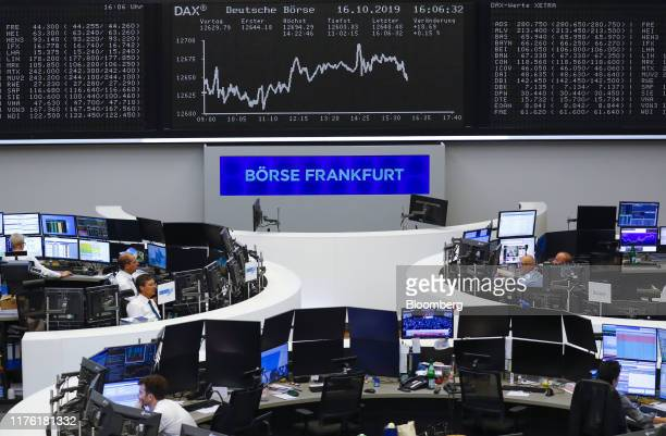 Traders sit in trading floor pods beneath the DAX Index curve and stock price information inside the Frankfurt Stock Exchange, operated by Deutsche...
