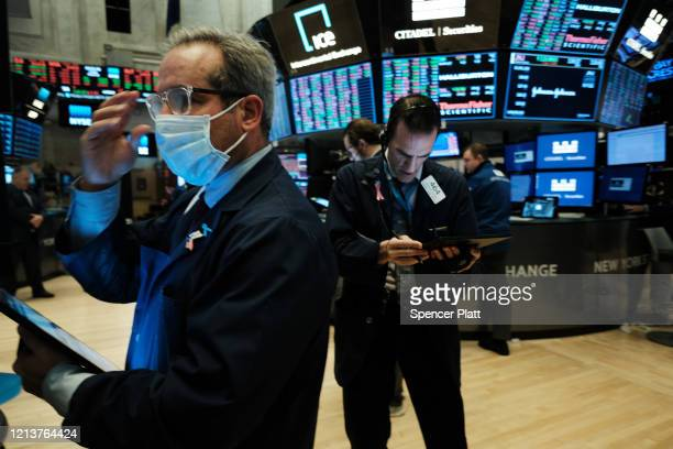 Traders, some in medical masks, work on the floor of the New York Stock Exchange on March 20, 2020 in New York City. Trading on the floor will...