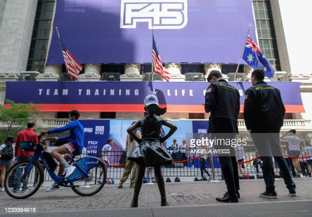 Traders stand in front of the New York Stock Exchange at Wall Street as the international fitness community F45 goes public on July 15, 2021 in New...