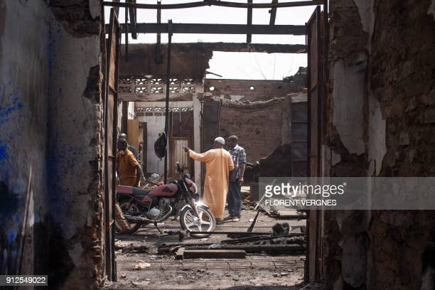 Traders stand in the rubble of a market after a blaze which damaged 47 shops on January 17 in Bangui's predominantly Muslim PK5 quarter on January 25...