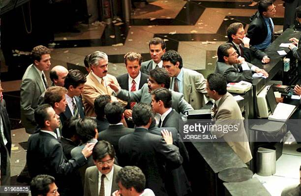 Traders talk on the floor of the Mexican stock exchange 30 January 1995 in Mexico City as the peso plunged in value falling in New York to 596 to the...