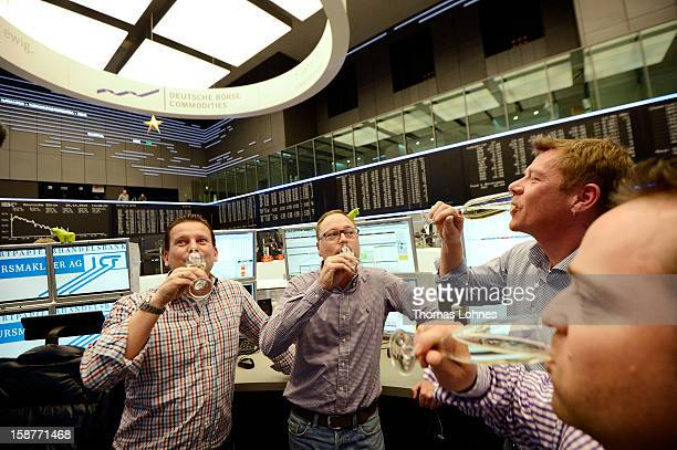 Traders toast one another with champagne on the last day of trading for 2012 at the Frankfurt Stock Exchange on December 28, 2012 in Frankfurt,...