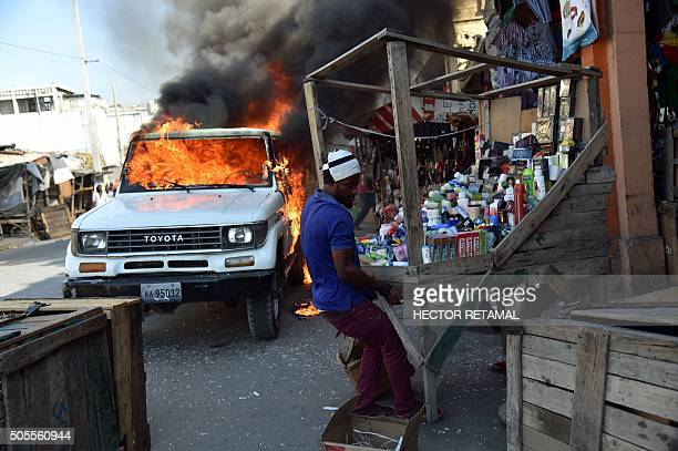 TOPSHOT Traders try to rescue their merchandise near a burning car during a protest in PortauPrince on January 18 2016 During the protest the...
