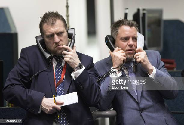 Traders use telephones as they work on the trading floor outside the open outcry pit at the London Metal Exchange at Leadenhall Street in London,...