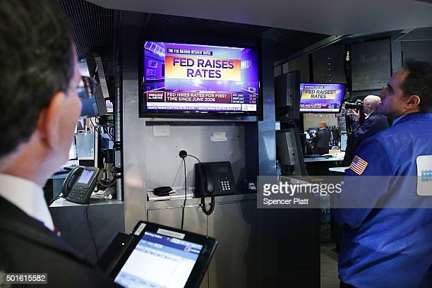 Traders wait on the floor of the New York Stock Exchange for the announcement that the Federal Reserve will raise interest rates for the first time...