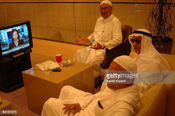 Traders watch a woman reading the television news while they wait for the latest shareprice updates at the NCB bank in Jeddah Saudi Arabia 2nd...