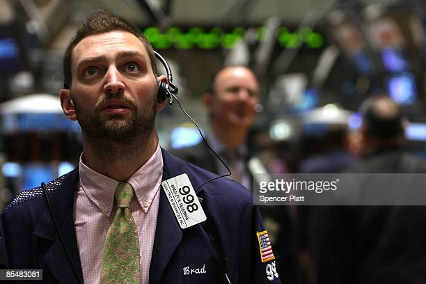 Traders watch news of the latest Fed numbers on the floor during afternoon trading at the New York Stock Exchange March 18 2009 in New York City With...