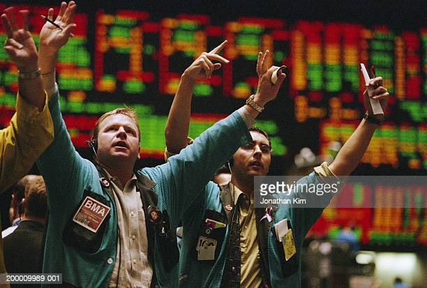 traders waving arms on exchange floor - börsensaal stock-fotos und bilder