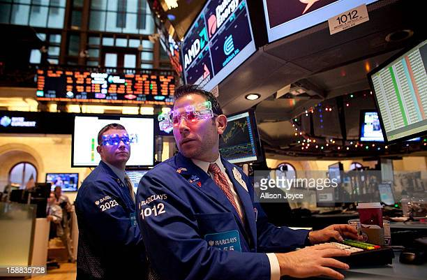 Traders wear 2013 New Years party glasses while they work on the floor of the New York Stock Exchange December 31 2012 in New York City US lawmakers...