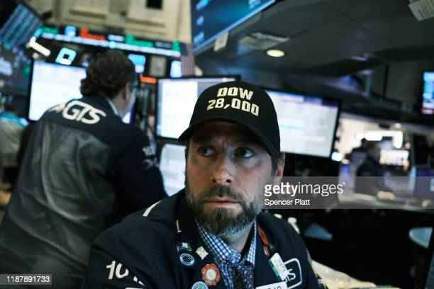 """Traders wear """"DOW 28,000"""" hats on the floor of the New York Stock Exchange on November 15, 2019 in New York City. As trade talks with China show some..."""