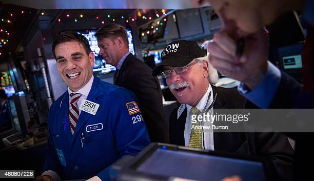 Traders wear hats that say DOW 18000 as they work on the floor of the New York Stock Exchange during the afternoon of December 23 2014 in New York...