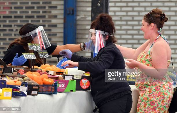 Traders wearing PPE including gloves and a visor as a precautionary measure against COVID19 serve customers at their fruit and vegetable stall at...
