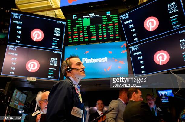 Traders work after the opening bell at the New York Stock Exchange , while logo for Pinterest Inc. Is pictured on the screens during the company's...