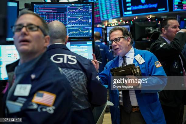 Traders work ahead of the opening bell on the floor of the New York Stock Exchange December 10 2018 in New York City The Dow Jones Industrial down...