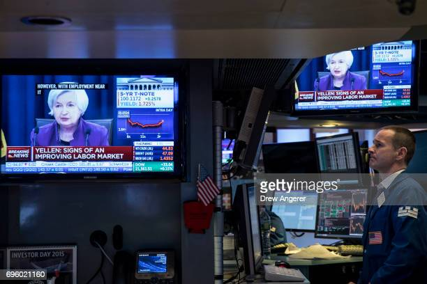 Traders work as a television monitor displays Federal Reserve Chair Janet Yellen announcing the Fed's decision to raise interest rates on the floor...