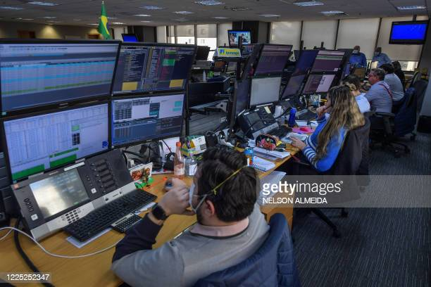 Traders work at the Necton brokerage company in Sao Paulo, Brazil on July 7 during the COVID-19 pandemic. - Brazilian President Jair Bolsonaro tested...