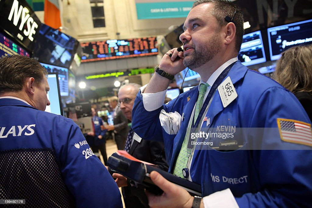 Traders work at the New York Stock Exchange (NYSE) in New York, U.S., on Monday, Jan. 14, 2013. U.S. stocks fell, after the Standard & Poor's 500 Index climbed for two weeks to trade near the highest level in five years, as Apple Inc. tumbled amid a report it cut orders for iPhone components. Photographer: Scott Eells/Bloomberg via Getty Images