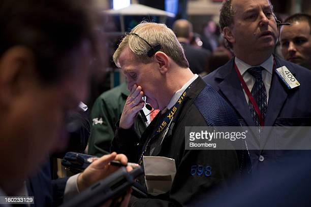 Traders work at the New York Stock Exchange in New York US on Monday Jan 28 2013 US stocks fell following the longest rally for the Standard Poor's...