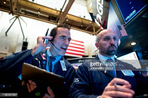 Traders work before the opening bell at the New York Stock Exchange on November 14 2019 in New York City Global economic worries on Thursday caused...