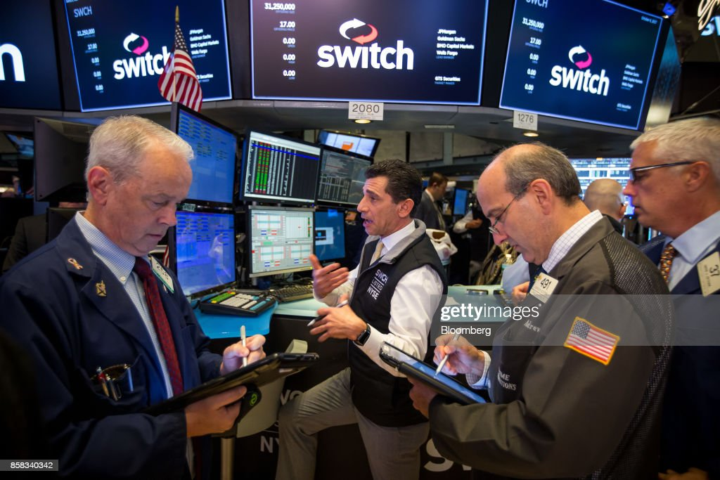 Traders work beneath a monitor displaying Switch Inc. signage on the floor of the New York Stock Exchange (NYSE) in New York, U.S., on Friday, Oct. 6, 2017. Switchjumped by almost half in its trading debut after raising $531 million in an initial public offering, the third-biggest technology IPO this year in the U.S. Photographer: Michael Nagle/Bloomberg via Getty Images