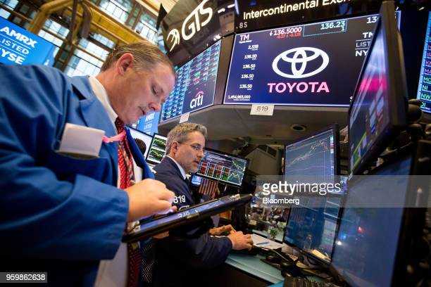 Traders work beneath a monitor displaying Toyota Motor Corp signage on the floor of the New York Stock Exchange in New York US on Friday May 18 2018...