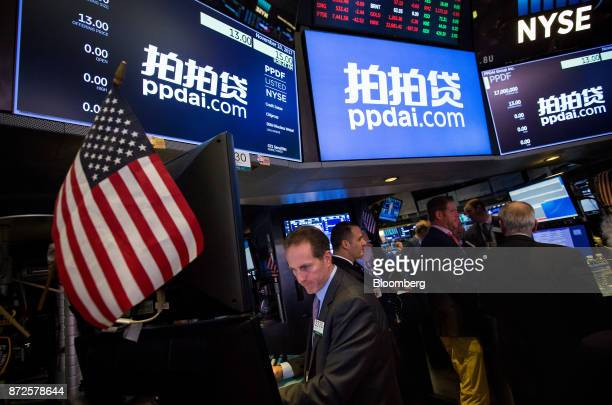 Traders work beneath monitors displaying PPDAI Group Inc signage on the floor of the New York Stock Exchange in New York US on Friday Nov 10 2017...