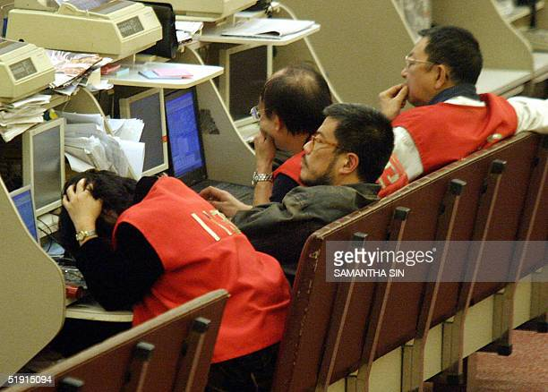 Traders work during afternoon session at the Hong Kong Stock Exchange 05 January 2005 Hong Kong share prices closed sharply lower Wednesday shedding...