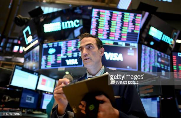 TOPSHOT Traders work during the closing bell at the New York Stock Exchange on March 18 2020 at Wall Street in New York City Wall Street stocks...