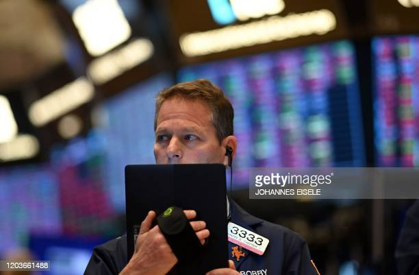 Traders work during the opening bell at the New York Stock Exchange on February 27, 2020 at Wall Street in New York City. - Wall Street stocks opened...