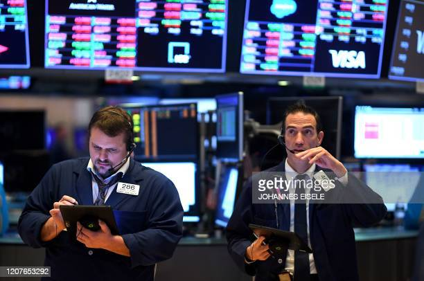 Traders work during the opening bell at the New York Stock Exchange on March 19 at Wall Street in New York City US stocks open mixed Dow 04% Nasdaq...