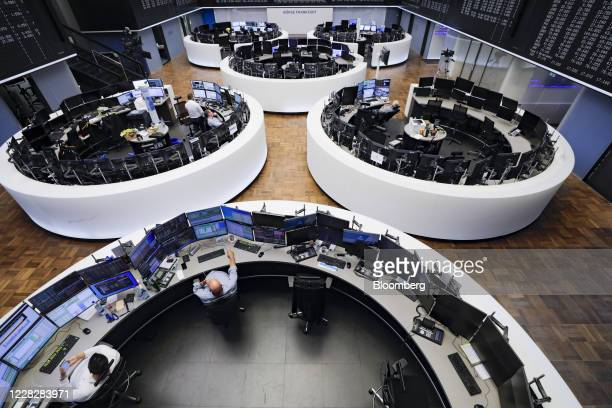 Traders work in a near empty trading floor at the Frankfurt Stock Exchange, operated by Deutsche Boerse AG, in Frankfurt, Germany, on Monday, Aug....