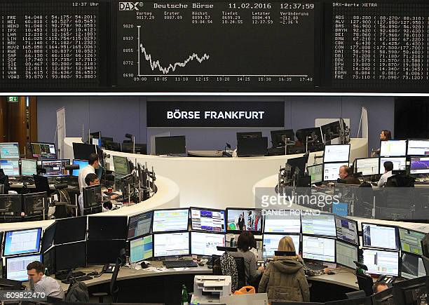 Traders work in front of a board displaying the chart of Germany's share index DAX at the stock exchange in Frankfurt am Main, western Germany, on...