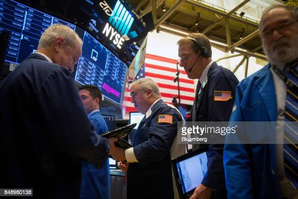 Traders work in front of a monitor displaying Equifax Inc signage on the floor of the New York Stock Exchange in New York US on Monday Sept 18 2017...