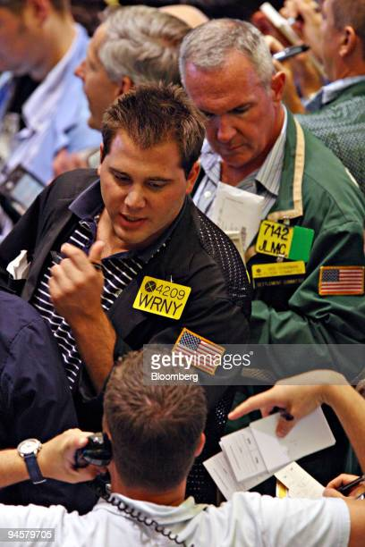 Traders work in the crude oil and natural gas options pit at the New York Mercantile Exchange, Tuesday, July 17 in New York. Crude oil was little...