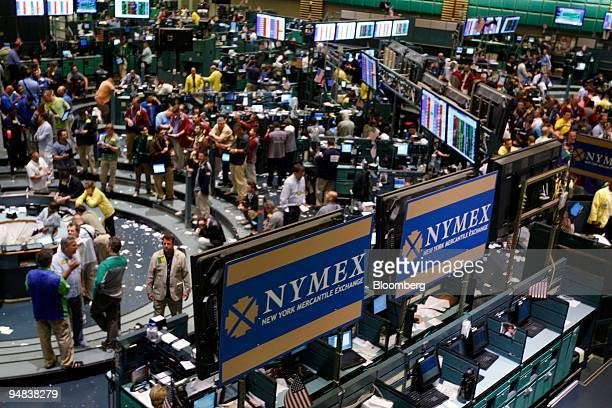 Traders work in the crude oil futures pit left at the New York Mercantile Exchange in New York US on Monday June 30 2008 Crude oil rose for a third...