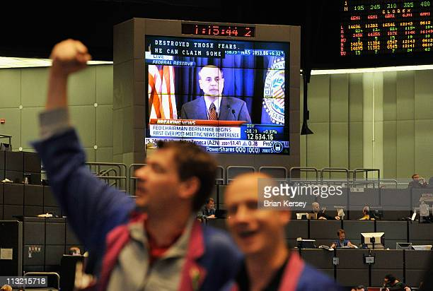 Traders work in the Dow Jones Industrial average futures pit as Federal Chairman Ben Bernanke is shown on a large television screen at the CME Group...