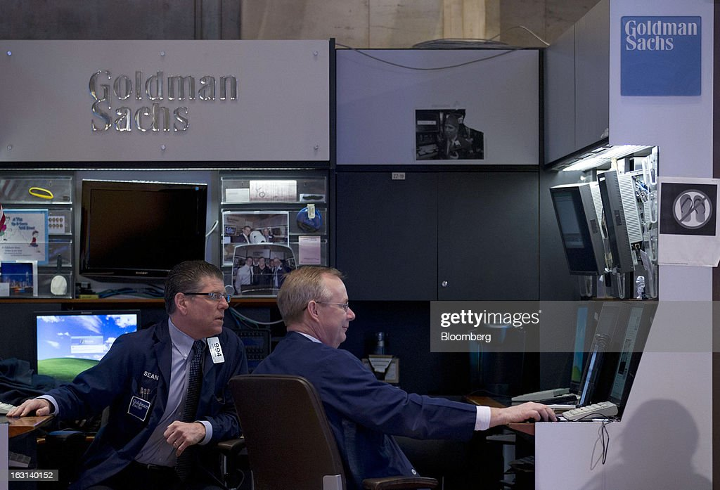 Traders work in the Goldman Sachs Group Inc. booth on the floor of the New York Stock Exchange (NYSE) in New York, U.S., on Tuesday, March 5, 2013. Stocks rallied, sending the Dow Jones Industrial Average to a record, and metals climbed as China vowed to maintain its growth target and investors bet central banks will continue stimulus measures. Treasuries fell for a second day and the dollar weakened against most peers. Photographer: Jin Lee/Bloomberg via Getty Images