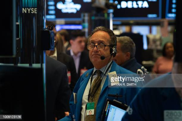 Traders work on the floor at the closing bell of the Dow Industrial Average at the New York Stock Exchange on August 1 2018 in New York Wall Street...