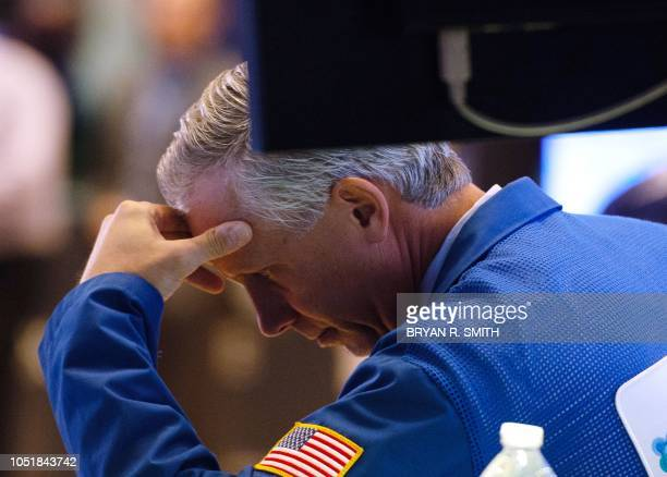 Traders work on the floor at the closing bell of the Dow Industrial Average at the New York Stock Exchange on October 10 2018 in New York Wall Street...