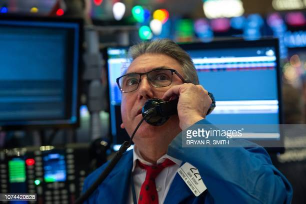 Traders work on the floor at the closing bell of the Dow Industrial Average at the New York Stock Exchange on December 19 2018 in New York Wll Street...