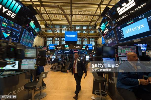 Traders work on the floor at the closing bell of the Dow Industrial Average at the New York Stock Exchange on September 14 2017 in New York The Dow...