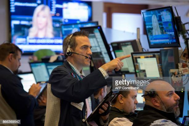 Traders work on the floor at the closing bell of the Dow Industrial Average at the New York Stock Exchange on October 25 2017 in New York The Dow...