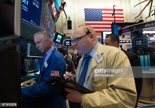 Traders work on the floor at the closing bell of the Dow Industrial Average at the New York Stock Exchange on November 8 2017 in New York Wall Street...