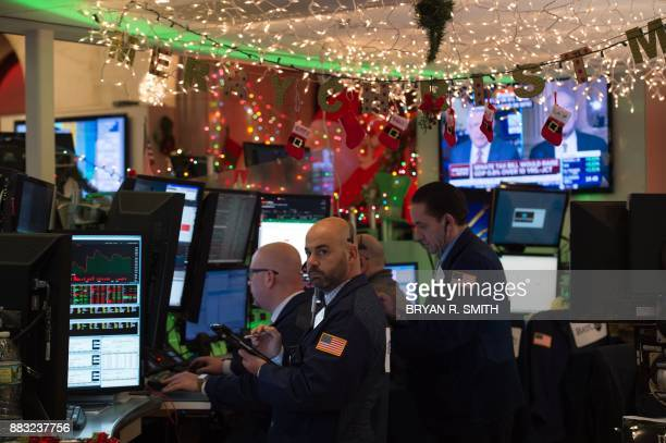 Traders work on the floor at the closing bell of the Dow Industrial Average at the New York Stock Exchange on November 30 2017 in New York / AFP...
