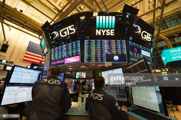Traders work on the floor at the closing bell of the Dow Industrial Average at the New York Stock Exchange on December 6 2017 in New York / AFP PHOTO...