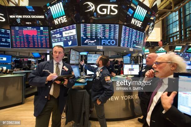 Traders work on the floor at the closing bell of the Dow Industrial Average at the New York Stock Exchange on January 30 2018 in New York Wall Street...