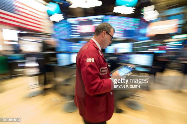 TOPSHOT Traders work on the floor at the closing bell of the Dow Industrial Average at the New York Stock Exchange on January 30 2018 in New York...