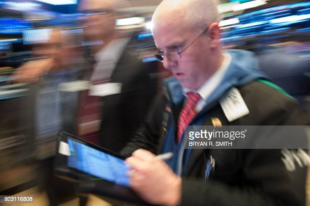 Traders work on the floor at the closing bell of the Dow Industrial Average at the New York Stock Exchange on February 22 in New York Wall Street...