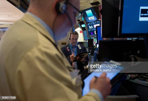 Traders work on the floor at the closing bell of the Dow Industrial Average at the New York Stock Exchange on March 1 2018 in New York / AFP PHOTO /...